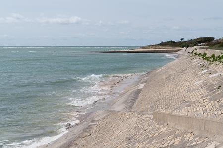 Dutch dike by atlantic ocean sea made of concrete stones