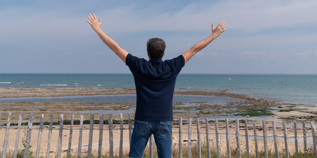 happy man raise hands on beach background in feel good and freedom concept Banque d'images