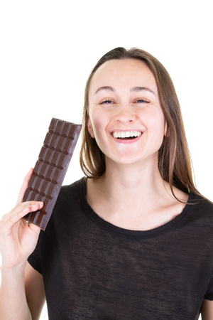 Beautiful young woman eating smiling bar chocolate