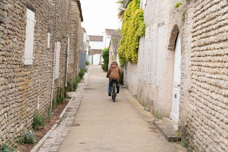 senior woman on bike in alleys on the Ile de Re in France