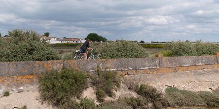 side view young woman cycling at seaside dike on island Ile de Re in France