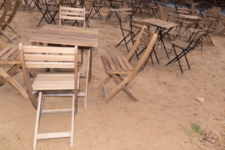 wooden table place and chairs on sandy beach