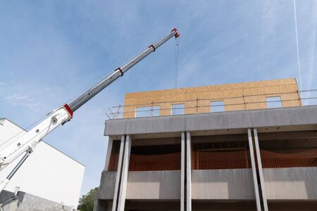 Construction site crane is lifting a precast wooden wall panel 스톡 콘텐츠