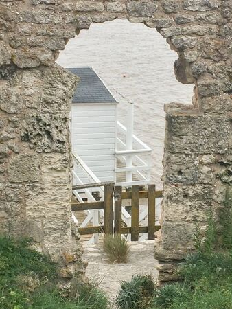 view of fishermen huts through an old medieval stone gate