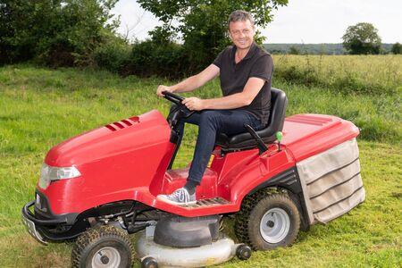 Gardner man on ride-on lawn mower gardener in garden