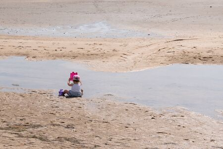 Cute baby girl with hat sitting on the sand on seashore and play bucket in water sea