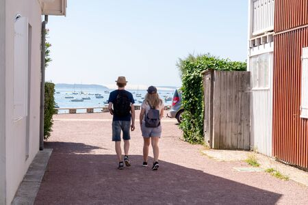 young tourist couple in oyster village Le Canon in Cap Ferret France in back view Foto de archivo