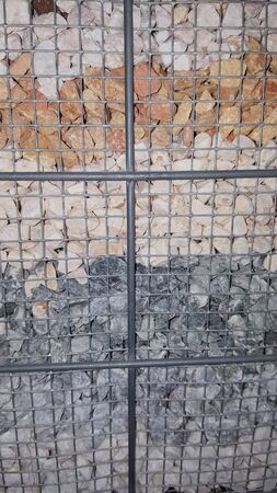 different stones in metal cage for outdoor decoration