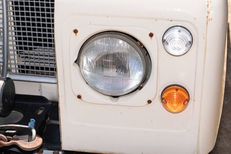 Glass headlight of an old retro truck SUV all-terrain sand colour