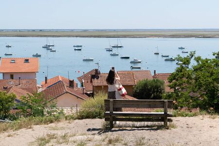 tourist young woman take phone picture in basin Cap Ferret Arcachon in french village Herbe