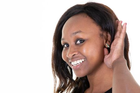 Beautiful african woman holding hand near ear trying to listen interesting communication in white background