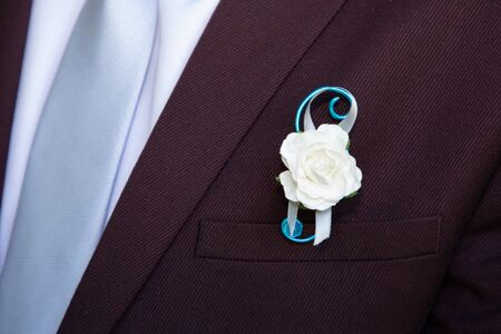 detail groom wearing floral pins decoration jacket corsage
