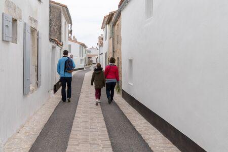 widok z tyłu turystyczna rodzina spacerująca po ulicy w wiosce Saint Martin de Re położonej na Ile de Re we Francji? Zdjęcie Seryjne