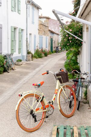 street in Ile de Re with white house green shutter and beach cruiser bike