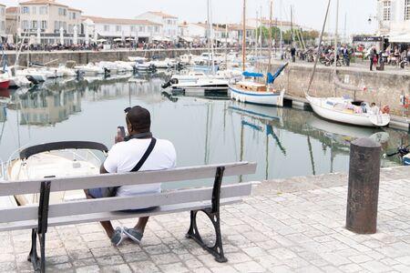 african american man tourist looking port harbor of St Martin de ré in Ile de Re in France Stock fotó