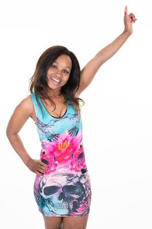 Feliz mujer africana americana apuntando hacia arriba los dedos de la mano y sonriendo sobre fondo blanco.