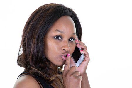 femme afro-américaine noire parlant au téléphone et tenant son doigt sur ses lèvres dans un geste calme chut