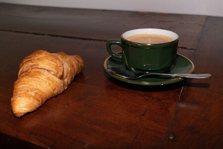 coffee and croissant on wooden table