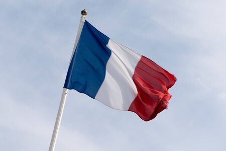Flag of France waving over a cloud sky