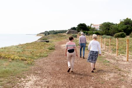 healthy senior attractive man woman group hiking in Vendee sea coast
