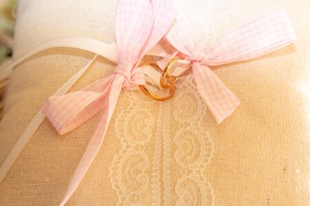 wedding rings on a white cushion with pink laces