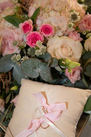 Wedding rings on a pillow cushion with bouquet flowers
