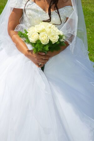 bride in white marriage dress holding flowers wedding bouquet