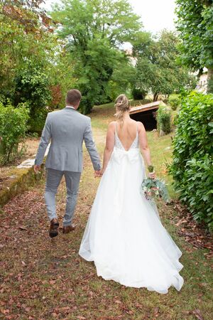 charming and beautiful couple in wedding day walking outside Stock Photo