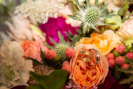 wedding rings on marriage flowers bouquet Stock Photo