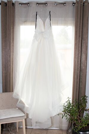 white wedding dress hanging on a window