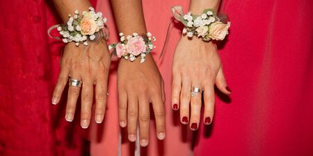 bride bridesmaids with red pink dress and flowers bracelets on hands in web banner template banner Banque d'images - 132113729