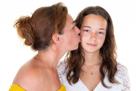 two caucasian lovely women adult mother kiss cheek her teenage daughter girl standing isolated over white background