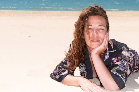 middle aged woman enjoy vacation by sea lying on sand beach