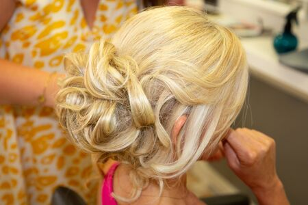 Hairdresser doing hairstyle for young woman blonde curly hair