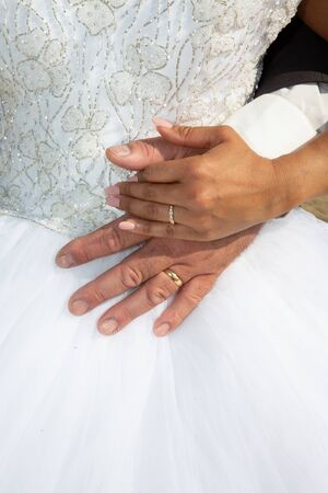 Wedding rings and hands groom bride