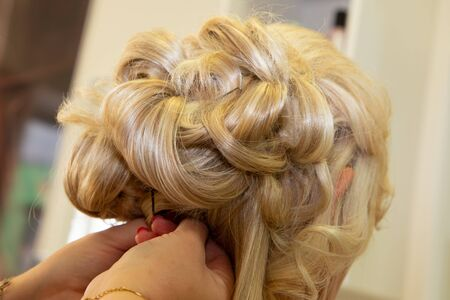 hair stylist artist prepare a blonde woman bride for the wedding day