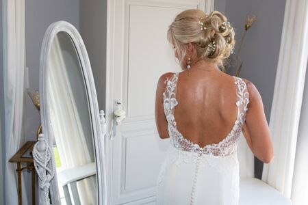 Girl bride in a white dress at the mirror in wedding day