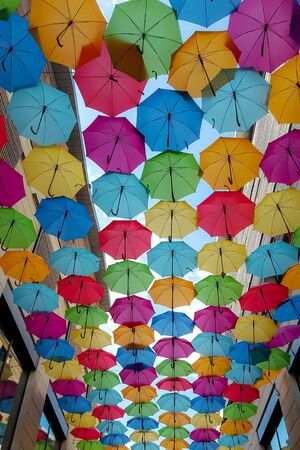 Street decoration with colorful open umbrellas in background hanging over city alley