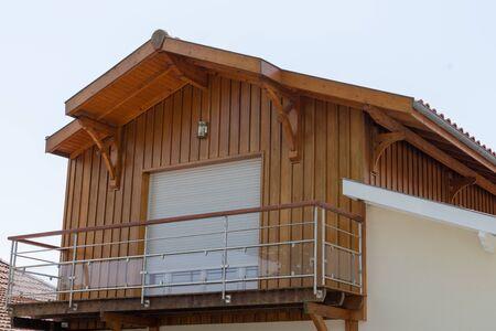 saubere Holzfassade mit Fenster des modernen Holzhauses mit transparentem Glasgeländer