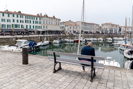 Saint Martin de  Re, Charente Maritime  France - 05 01 2019 : young bald man surfing texting in smartphone in St Martin de Ré