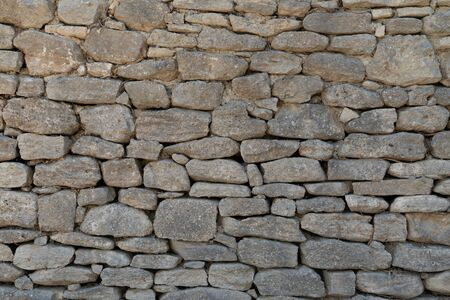 Old gray wall made of large and small rectangular hewn natural stones