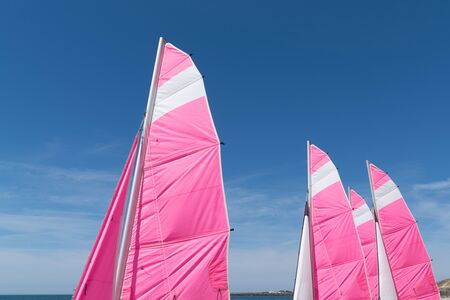 Colorful view of sail tops of sailing boats in beautiful blue sky day on the beach