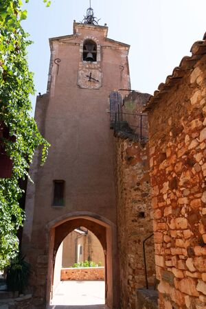 narrow street in French village of Roussillon buildings colorful ochre in France Stok Fotoğraf