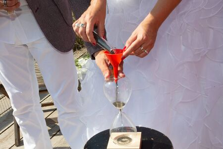 Closeup view of bride and groom during wedding sand ceremony symbol of unity