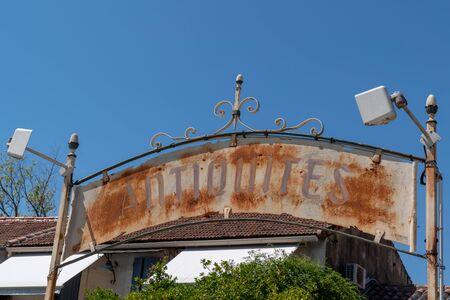 rusty Antiques Shop Sign means Antiquites in French city isle sur la sorgue