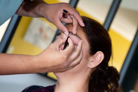 Professional stylist woman doing make-up for brunette bride Stock Photo