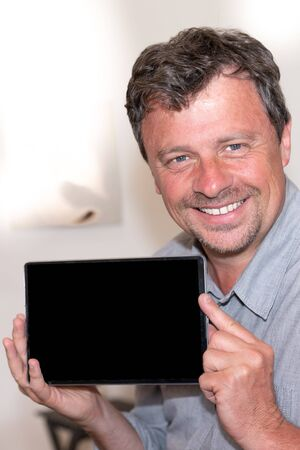 smiling man handsome is holding tablet with a blank screen black indoor Stockfoto