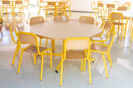 Empty school canteen yellow table and chairs Standard-Bild