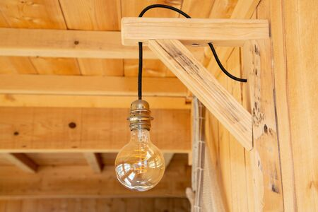 Vintage incandescent light bulb illuminates on wooden wall room background