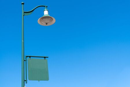 real old vintage green lamp post with an empty sign banner in blue sky